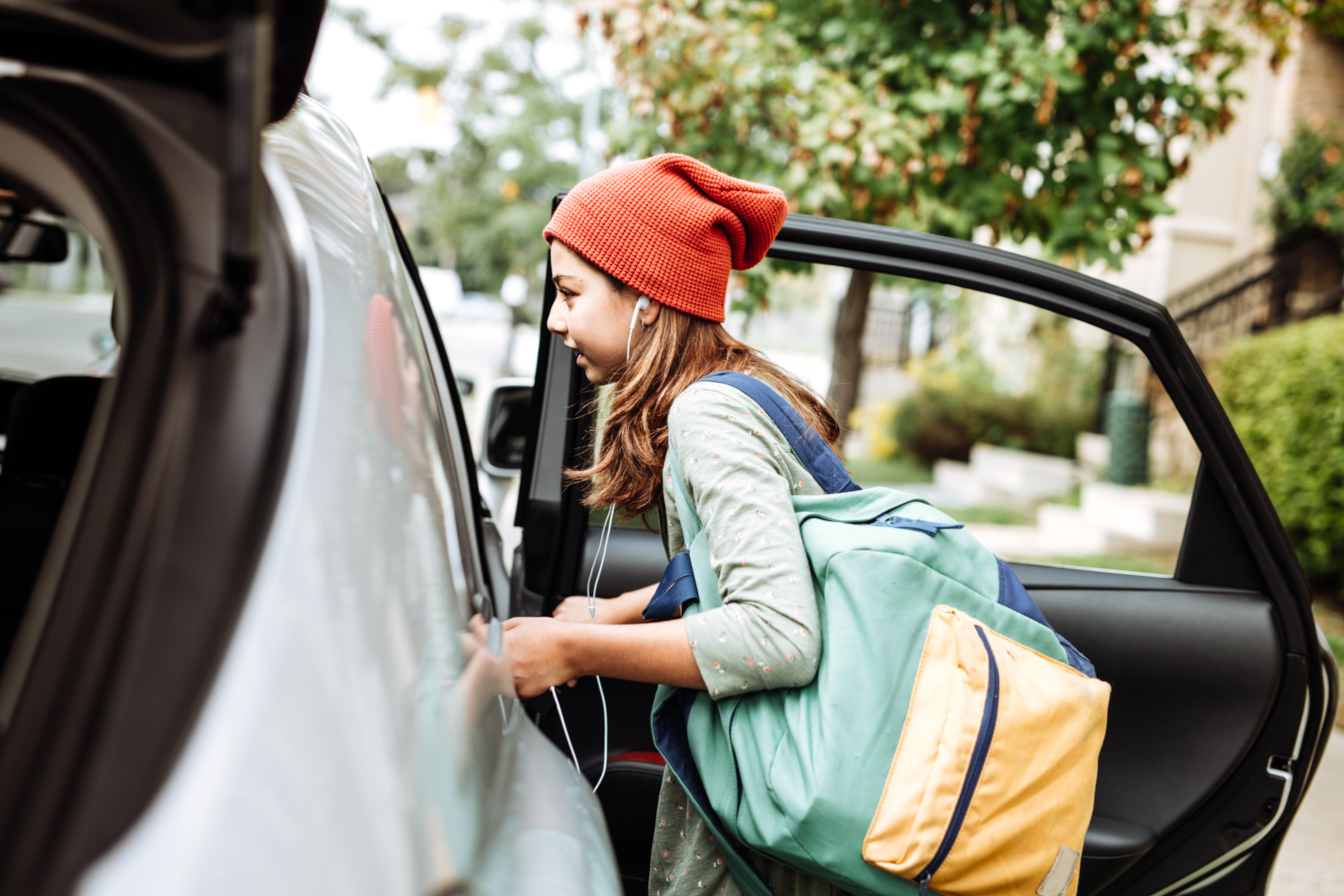 Girl getting in car to go to school